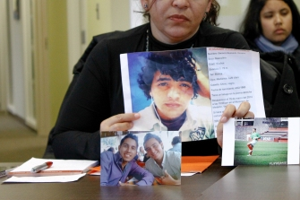 Maricela Orozco displays photos of her sons, one of whom was disappeared. Maricela's youngest son was murdered alongside Maricela's son-in-law.