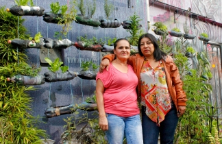 "Women Walking for Truth members Blanca Nidia Perez Botero (right) and Luz Elena Galeano Laverde (left) outside of ""La Casa Morada,"" an activist meeting space in the Comuna 13 neighborhood of Medellín."