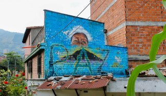 """Orion never again"" reads a mural commemorating 14 years since Operation Orion laid seige to the neighborhood of Comuna 13 in Medellín, Colombia's second largest city. The eyes of human rights activist Luz Elena Galeano Laverde look on as peace grows and origami doves flutter."