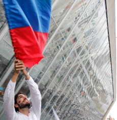 Pro-peace supporter waved a Colombian flag as thousands of marchers gathered in Medellín's Park of Lights (seen reflected in the windows of the EPM Library).