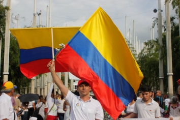 Pro-peace supporter waves the Colombian flag as he joins thousands of others in the Park of Lights in downtown Medellín on October 7.